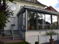 Wohnraumerweiterung in Holz-Rahmenbau mit Flachdach im Wintergartencharakter. Begehbare Terrasse auf dem Flachdach
